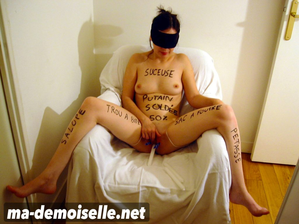 Une salope avec des inscriptions obscènes sur le corps se masturbe