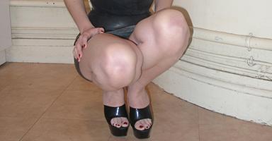 Salope accroupie en robe latex