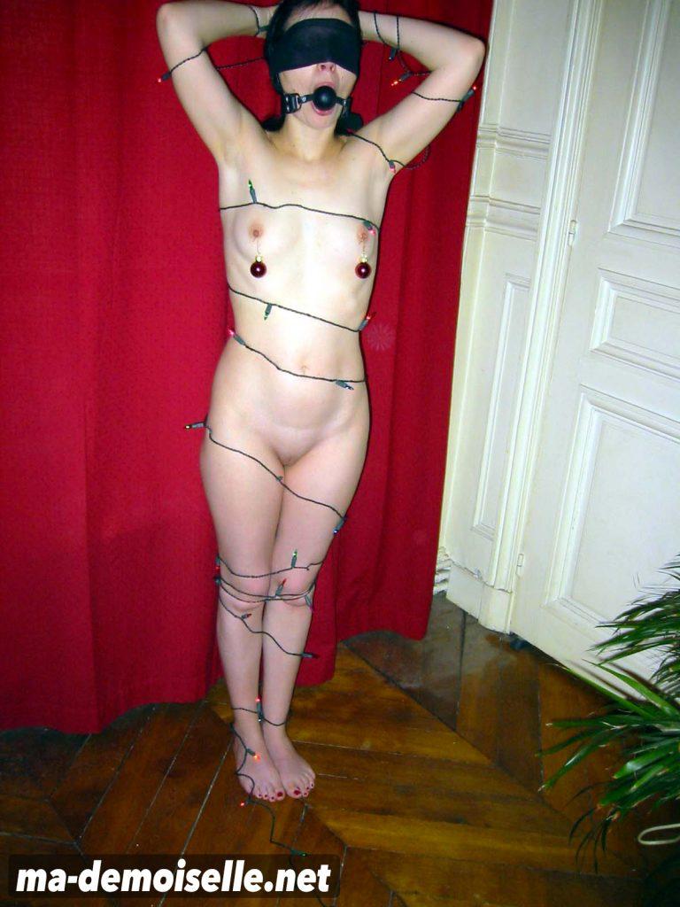 Jeune femme nue attachée et décorée en sapin de Noël
